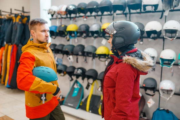 Young couple at the showcase trying on helmets for ski or snowboarding, side view, sports shop.