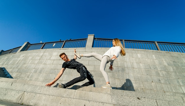 Young couple showing motions near the grey rock wall.flying hair. motion picture. woman knocks a man with a leg. stylish photo. blue sky above.