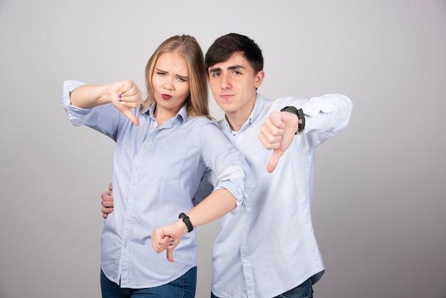 부정적인 표정으로 엄지손가락을 아래로 보여주는 젊은 부부.