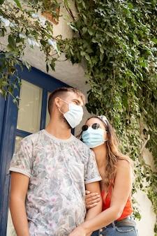パンデミックの時期に観光する若いカップル。彼らはフェイスマスクを着用しています。