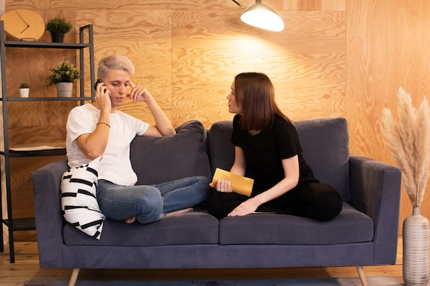 Young couple sits on the couch and swears. girl is very unhappy