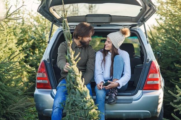 若いカップルはプランテーションで切りたてのクリスマスツリーを持って彼らのsuvのトランクに座っています