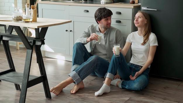 Молодая пара сидит на полу своей кухни и пьет вкусное молоко