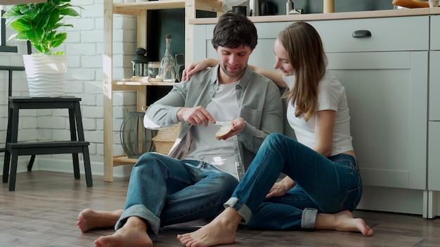젊은 부부는 부엌 바닥에 앉아 빵에 버터를 퍼뜨립니다.