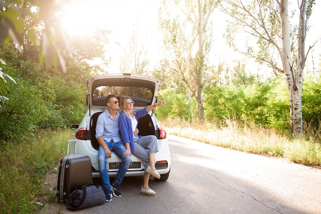 Young couple sits in the trunk of a car and chooses where to travel