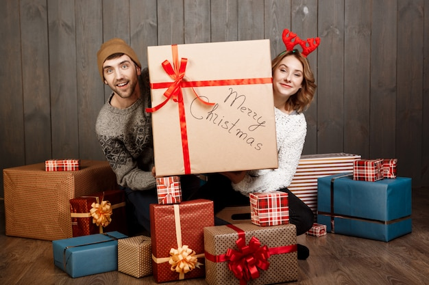 Young couple sitting among christmas gift boxes over wooden wall