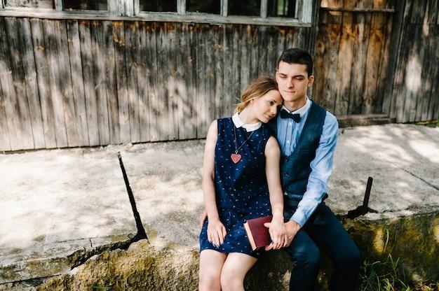 座っていると抱き締める若いカップルは閉じた本を保持します