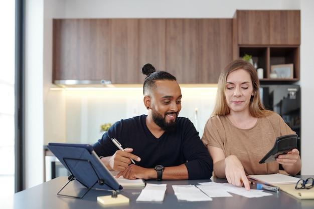 식탁에 앉아 청구서와 급여를 확인하고 가족 지출을 계산하는 젊은 부부
