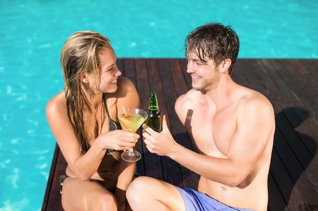 スイミングプールに座っている若いカップル