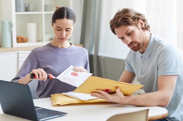 テーブルに座って、家で一緒に小包を開く若いカップル