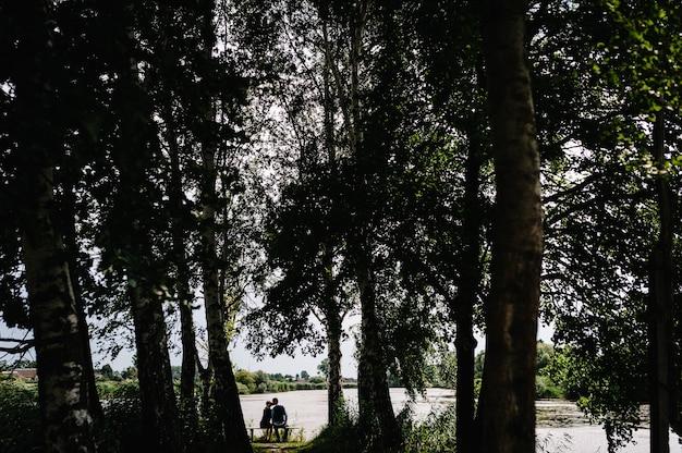 Молодая пара сидит спиной, целоваться и обниматься возле озера через лес