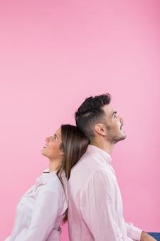 Молодая пара сидит спиной к спине