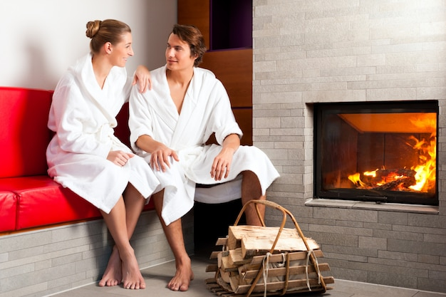 Young couple sitting in bathrobe for open fireplace