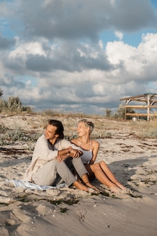Young couple sitting on the beach and smiling