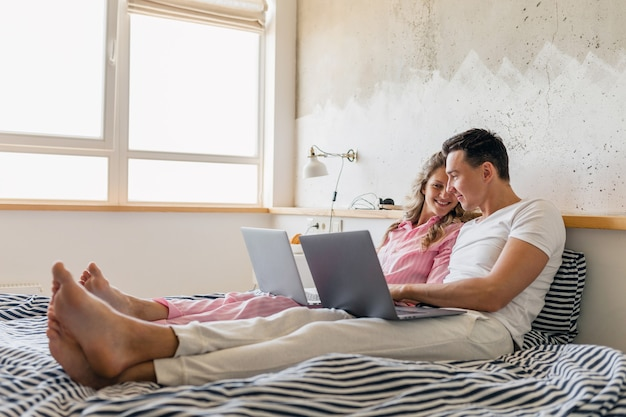 Young couple sitting on bed in morning, man and woman working on laptop