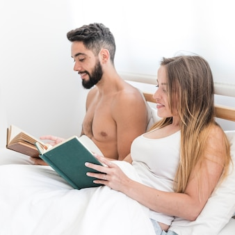 Young couple sitting on bed reading book