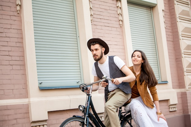 Young couple sitting on a bicycle against the wall