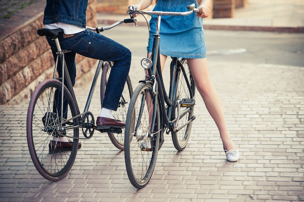 Young couple sitting on a bicycle opposite the city