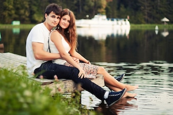 Young couple sitting by the pond