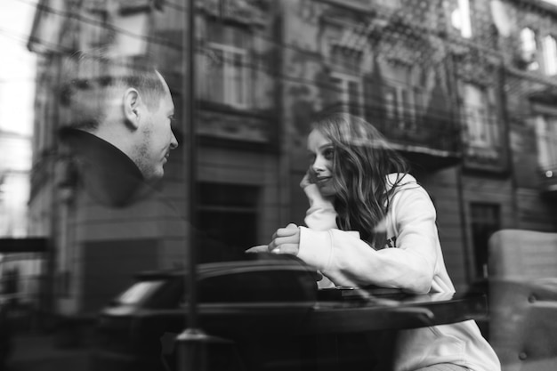 Young couple sitting in a cafe behind the window
