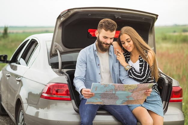Young couple sitting in the car trunk looking at map