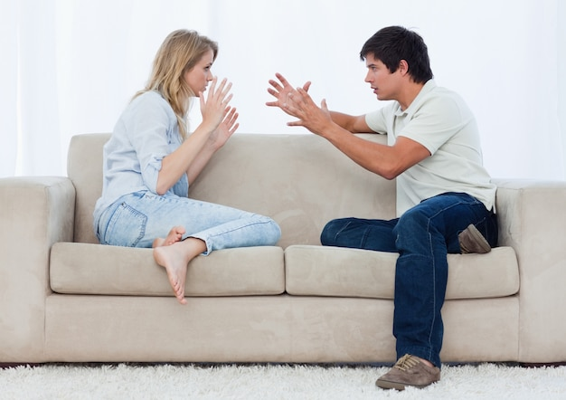 A young couple sitting on a couch are having an argument