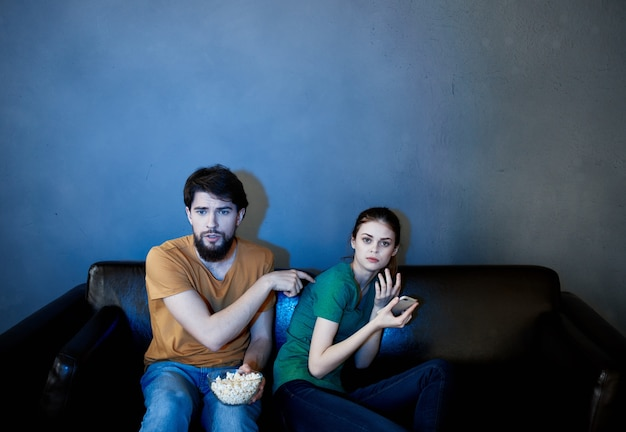 Young couple sitting on the couch in the evening watching scary movie