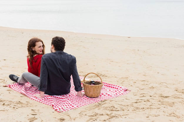 Young couple sitting on coverlet on sea shore