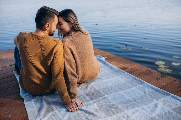 Young couple sitting on deck bridge by the river