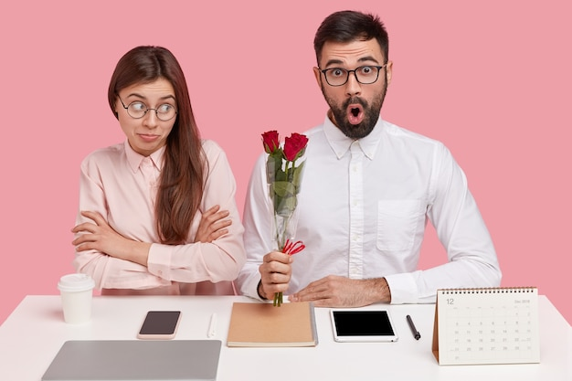 Young couple sitting at desk and man holding bouquet of roses