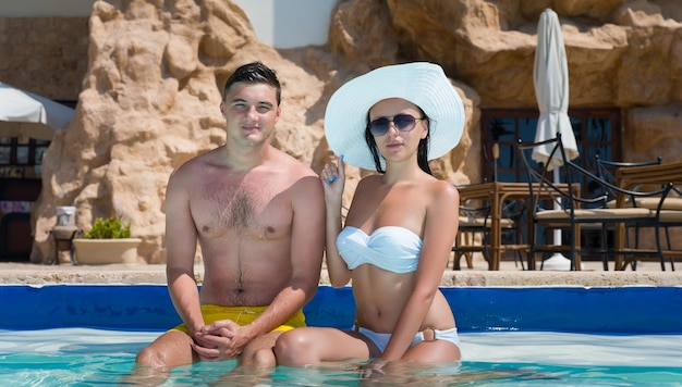 Young couple sitting on the edge of swimming pool at the hotel on a sunny summer day