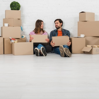 Young couple sitting on floor holding cardboard boxes in hand looking to each other