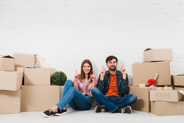 Young couple sitting on floor holding their fingers upward sitting between the cardboard boxes