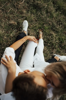 Young couple sitting on the green grass in a summer park, hugging and kissing. selective focus, focus on hand.