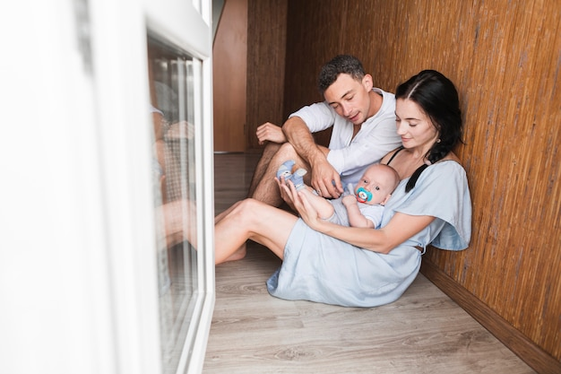 Young couple sitting on hardwood floor playing with their baby