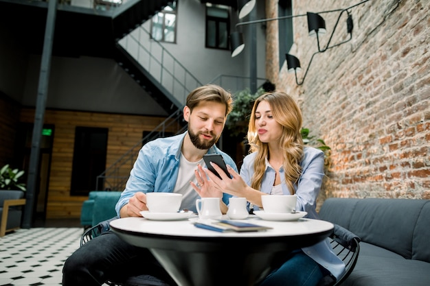 Young couple sitting in hotel lobby at the table and drinking coffee, using cell phone, smiling.