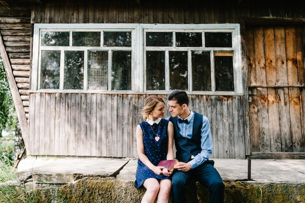 A young couple sitting and hugging holds a closed book in his hands near a wooden old house