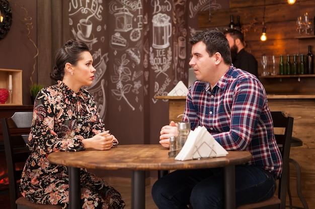 レストランに座って話し、楽しい時間を過ごしている若いカップル。