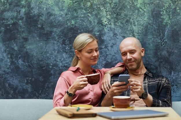 Молодая пара вместе сидит в кафе, используя мобильный телефон и пьет кофе