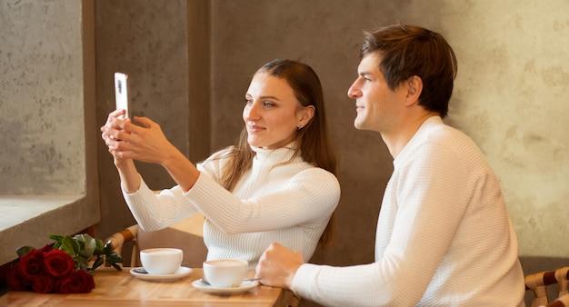 커피와 함께 카페에 앉아 젊은 부부. 장미 꽃다발.
