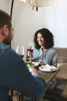 레스토랑에 앉아서 레드 와인을 마시는 젊은 부부. 샐러드를 먹고 카페에서 와인을 마시는 꽤 아프리카 계 미국인 여자