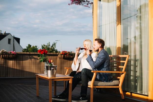 와인을 마시는 옥상 레스토랑에 앉아 젊은 부부