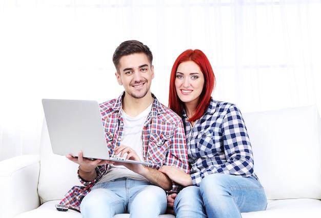 Молодая пара, сидя на диване с ноутбуком в комнате