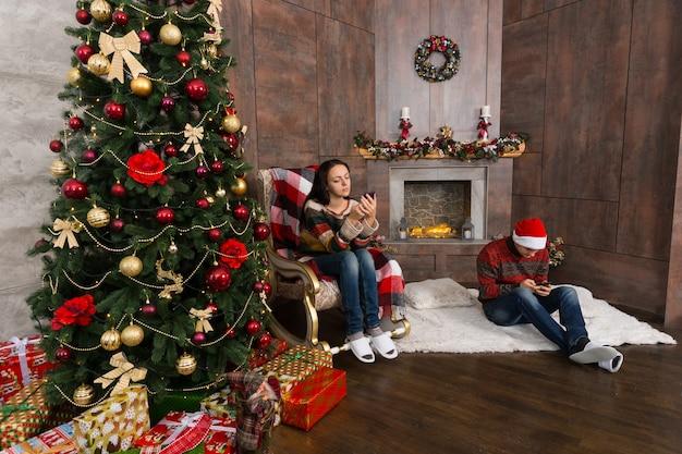 装飾された暖炉とプレゼントとクリスマスツリーのある部屋に座って、携帯電話でインターネットを提供している若いカップル