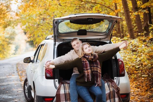 秋の道路で車のトランクに座っている若いカップル