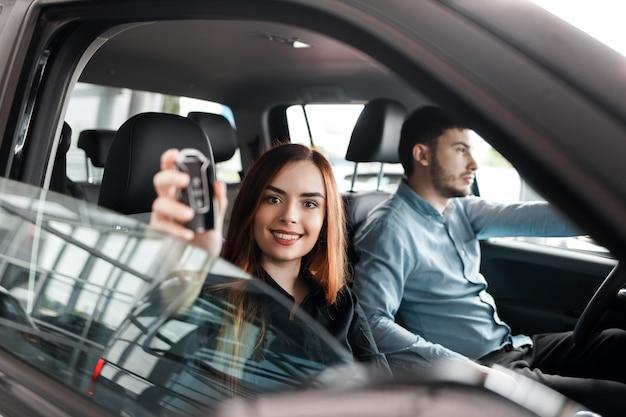 그들의 새로운 차 안에 앉아있는 젊은 부부