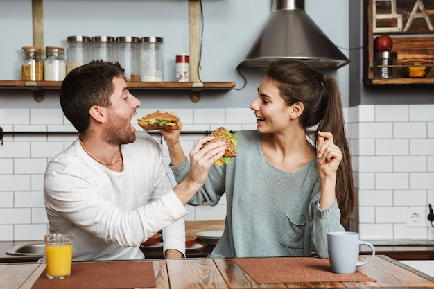 Young couple sitting at the kitchen during breakfast at home, feeding each other with sandwiches