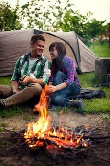 キャンプファイヤーの近くに座ってマシュマロを乾杯する若いカップル