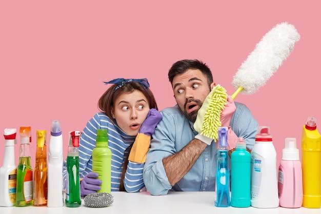 Молодая пара, сидящая рядом с чистящими средствами