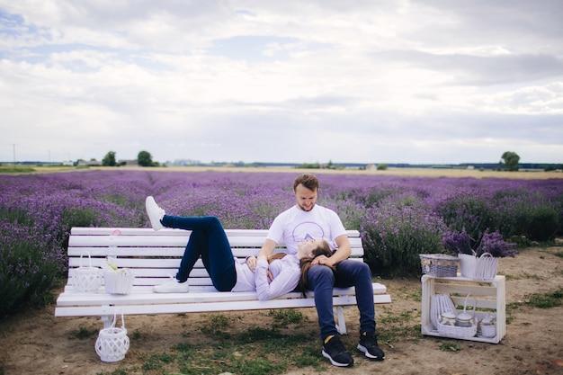 Молодая пара, сидящая на скамейке в лавандовом поле